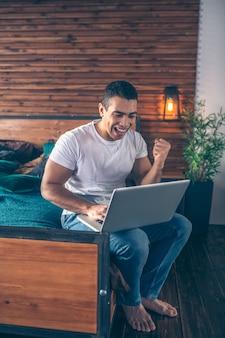 Joven de pelo oscuro en jeans sentado en la cama con su computadora portátil