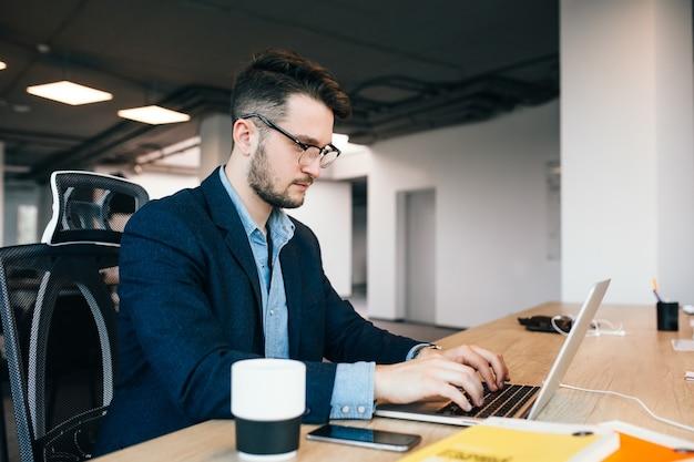 Joven de pelo oscuro está trabajando en la mesa en la oficina. viste camisa azul con chaqueta negra. está escribiendo en la computadora portátil y parece ocupado.