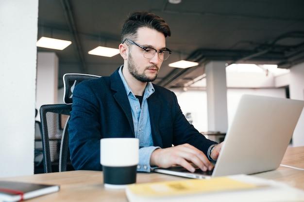 Joven de pelo oscuro está trabajando en la mesa en la oficina. viste camisa azul con chaqueta negra. está escribiendo en la computadora portátil en serio.
