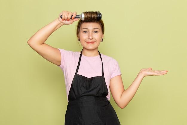 Una joven peluquera de vista frontal en camiseta rosa y capa negra arreglando su cabello con cepillo sonriendo en verde