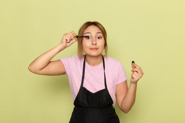 Una joven peluquera de vista frontal en camiseta rosa y capa negra haciendo maquillaje en verde
