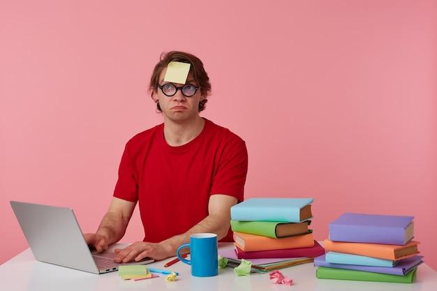 Joven pensador con gafas viste una camiseta roja, con una pegatina en la frente, se sienta junto a la mesa y trabaja con un cuaderno y libros, mira hacia arriba y supone, aislado sobre fondo rosa.