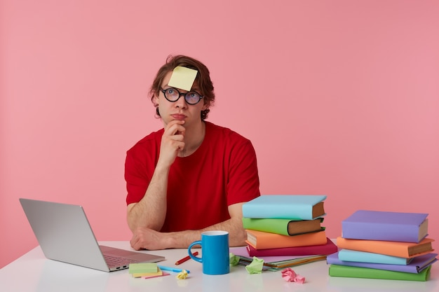 Joven pensador con gafas viste una camiseta roja, con una pegatina en la frente, se sienta junto a la mesa y trabaja con un cuaderno y libros, mira hacia arriba y toca la barbilla, aislado sobre fondo rosa.