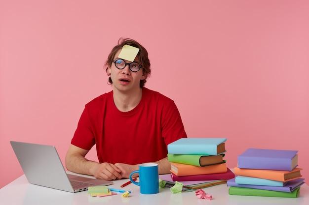 Joven pensador con gafas viste una camiseta roja, se sienta junto a la mesa y trabaja con un cuaderno y libros, con una pegatina en la frente, mira hacia arriba y cepilla, aislado sobre fondo rosa.