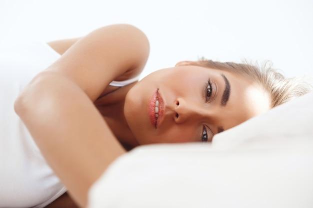Joven pensativa hermosa mujer acostada en la cama temprano en la mañana