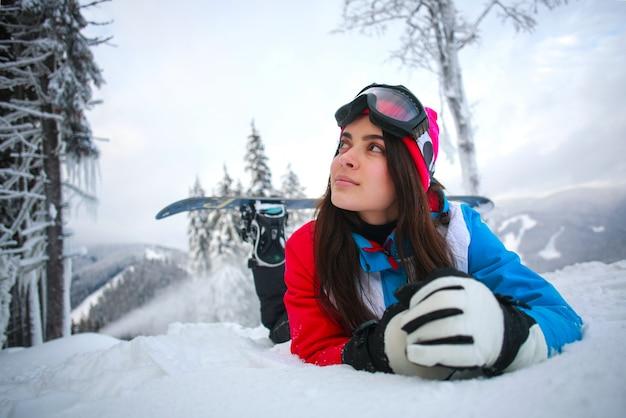 Joven pensativa en invierno en bosque nevado en la cima de las montañas