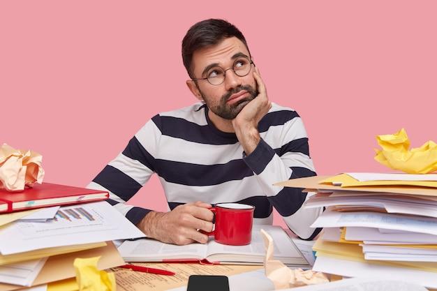 Joven pensativo tiene expresión contemplativa, sostiene la mano debajo de la barbilla, usa un jersey de rayas, bebe bebidas frescas, rodeado de una pila de libros de texto