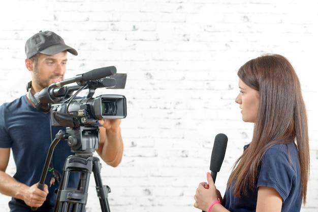Joven periodista con micrófono y camarógrafo