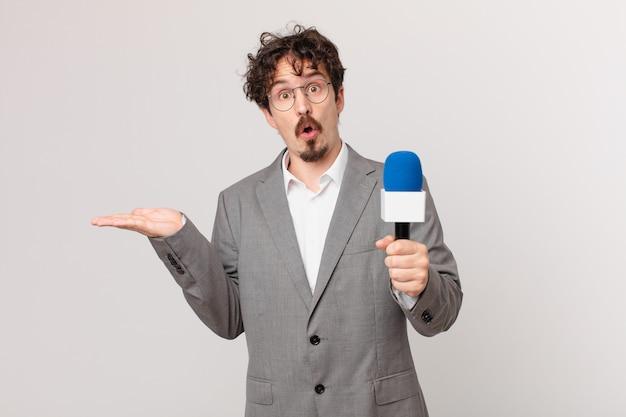 Joven periodista mirando sorprendido y conmocionado, con la mandíbula caída sosteniendo un objeto