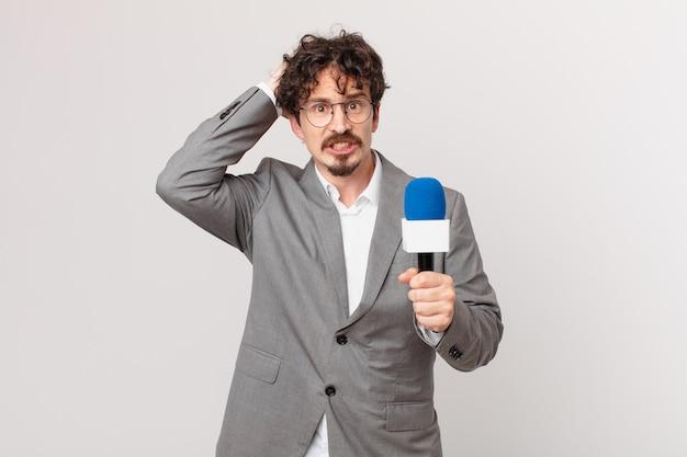 Joven periodista sintiéndose estresado, ansioso o asustado, con las manos en la cabeza