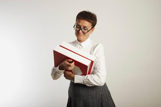 Joven pero anticuada profesora mira nuevas carpetas rojas y blancas con disgusto en blanco