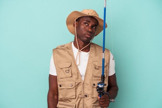 Joven pescador afroamericano sosteniendo la caña aislada sobre fondo azul soñando con lograr metas y propósitos