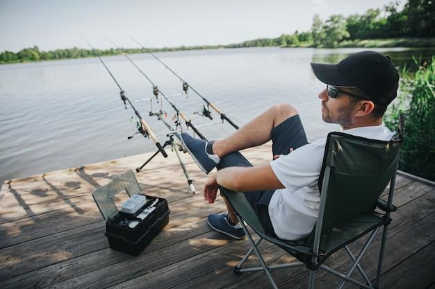 Joven pescador pescando en lago o río. vista lateral del chico adulto sentado en una silla plegable solo en la orilla del río o del lago. hombre pescando con tres cañas a su lado en el agua.