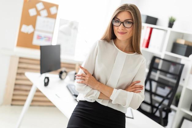 Una joven está de pie apoyándose en una mesa en la oficina.