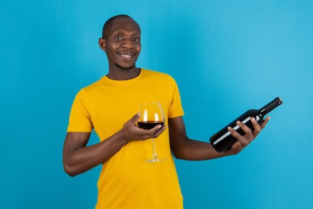 Joven de piel oscura con camisa amarilla con vino tinto en la pared azul