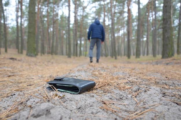 Joven pierde su bolso con billetes de dinero euro en el camino de madera de abeto de otoño ruso. descuido y perder el concepto de billetera