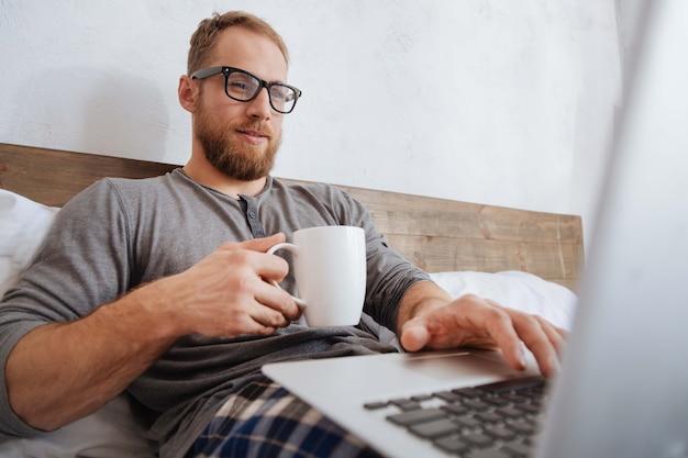 Joven en pijama disfrutando del proceso de trabajo mientras sostiene una taza de café y mira en la pantalla de una computadora portátil en la cama
