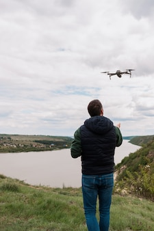 Joven pilotando un avión no tripulado en la naturaleza