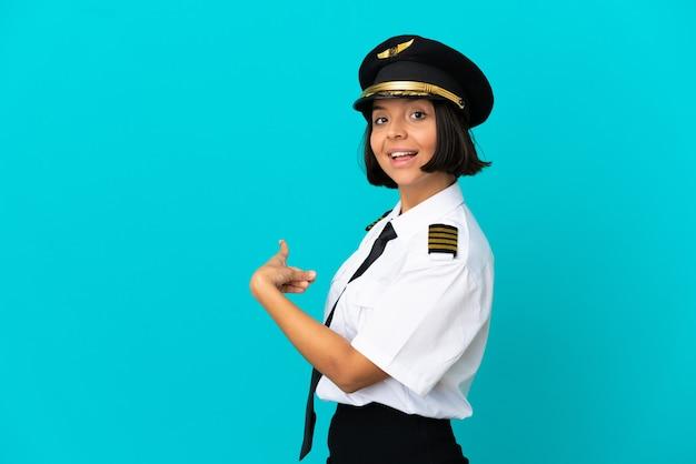 Joven piloto de avión sobre fondo azul aislado apuntando hacia atrás