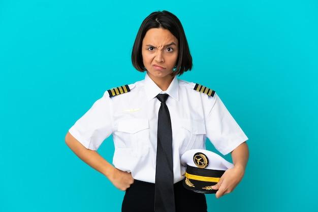 Joven piloto de avión sobre fondo azul aislado enojado