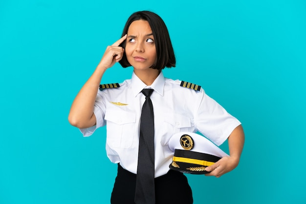 Joven piloto de avión sobre fondo azul aislado teniendo dudas y pensando