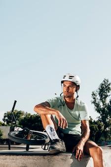 Joven piloto de bmx descansando en skatepark