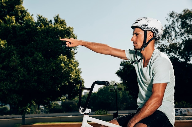 Joven piloto de bmx en su bicicleta señalando tiro medio