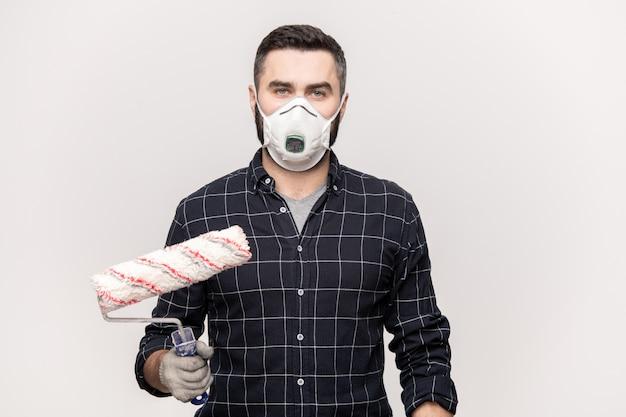 Joven pintor masculino serio con rodillo va a pintar paredes de habitación dentro de casa nueva