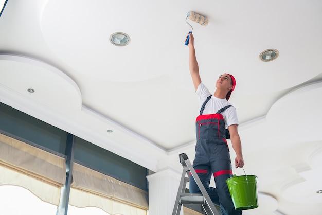 Joven pintor pintando el techo en concepto de construcción