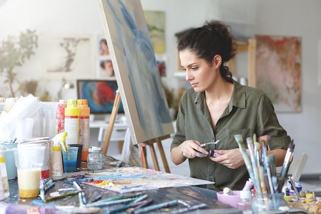 Joven pintora sentada en la mesa rodeada de varios pinceles y acuarelas mientras crea una bella imagen en el caballete. trabajador creativo trabajando en lienzo. concepto de arte y artesanía
