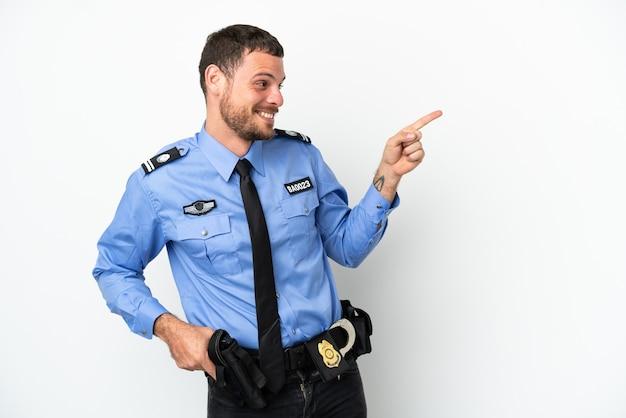 Joven policía brasileño aislado sobre fondo blanco apuntando con el dedo hacia un lado y presentando un producto