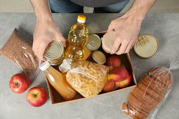 Joven pone comestibles en caja de donación. voluntario