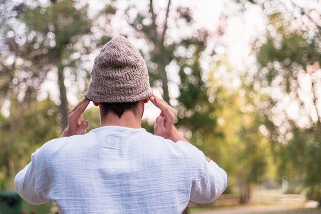 Joven se pone un sombrero para protegerse la cabeza del frío, está de espaldas.