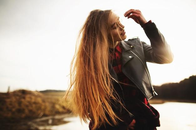 Una joven posa en la orilla de un lago.