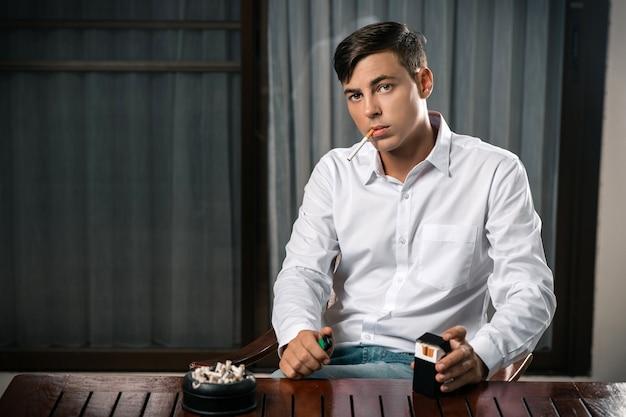 Un joven posa sentado en una mesa en la que se encuentra un cenicero lleno de cigarrillos.