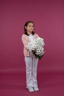 Una joven posa sobre un fondo rosa con flores en sus manos crisantemo