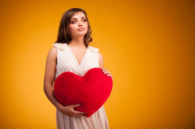 Joven positiva en vestido beige de pie, sosteniendo un gran corazón rojo en las manos y sonriendo sobre fondo amarillo oscuro