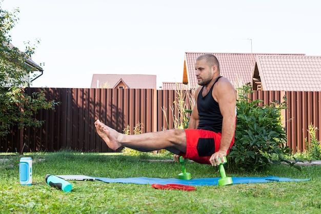El joven practica deportes en casa en el patio trasero en un día de verano. deportista con cabello negro sacude la prensa, hace ejercicio para bíceps, mantiene el equilibrio con mancuernas en el patio trasero
