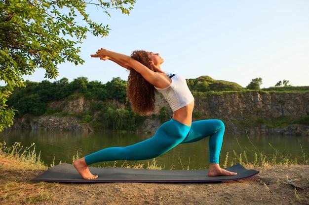 Joven practica yoga cerca del río