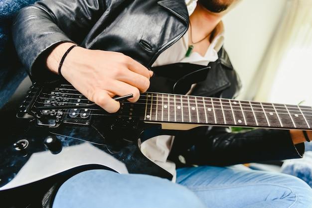 Joven practicando con su guitarra eléctrica en el sofá de su casa de aprendizaje.