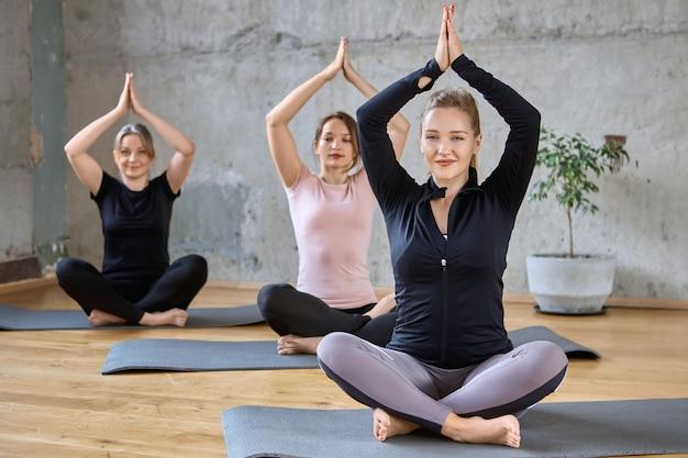 Joven practicando yoga pose en hall.