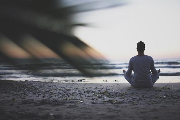 Joven practicar yoga en la playa al atardecer.