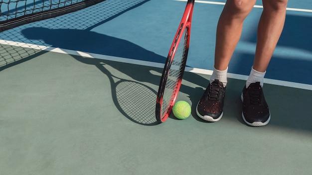 Joven preadolescente pies de niño con pelota de tenis verde y raqueta roja, deportes para niños, concepto de niño sano activo