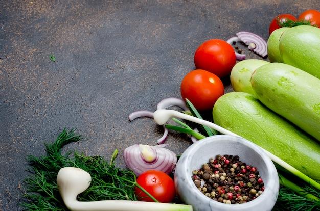 Joven primavera calabacín, tomates, hierbas y especias en negro