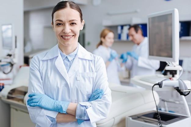 Joven profesional. atractivo trabajador médico de pie en primer plano, cruzando los brazos sobre el pecho mientras mira directamente a la cámara