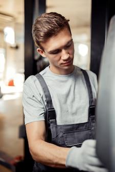 Un joven profesional está cambiando un neumático: la seguridad es lo primero. mantenimiento del auto.