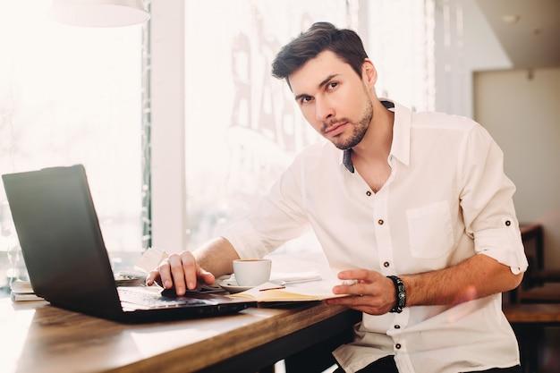 Joven profesional independiente masculino usando una computadora portátil mientras está sentado en la cafetería