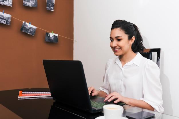 Joven profesional independiente que trabaja desde una improvisada oficina en casa conectada a internet con una computadora portátil y un teléfono.