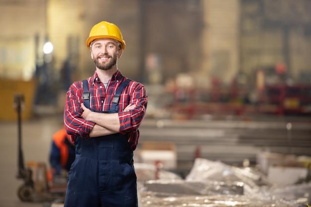 Joven profesional en la industria de pie dentro del taller de gran planta o fábrica
