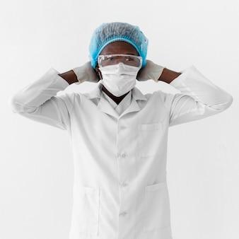 Joven profesional médico ajustando su máscara